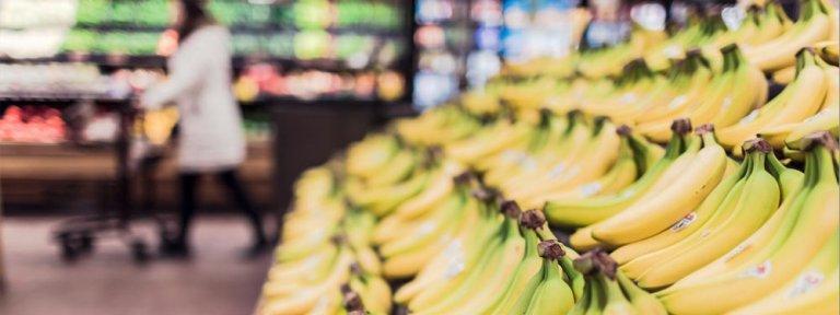 Bild zeigt eine Supermarktsituation und das große Angebot an Waren, hier Bananen. Wie unterscheiden die sich und wie machen die auf sich aufmerksam.