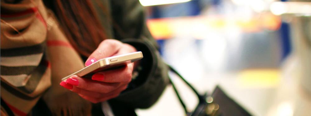 Der mobile Index wird von Google eingeführt. Das Bild zeigt eine Frau wie sie unterwegs auf ihr Smartphone schaut