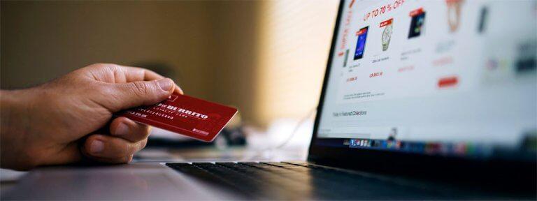 Foto zeigt einen Mann vor dem Laptop, mit einer Kreditkarte in seiner linken Hand. Auf dem Bildschirm ist ein Onlineshop zu sehen